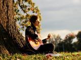 树下弹吉他的男孩
